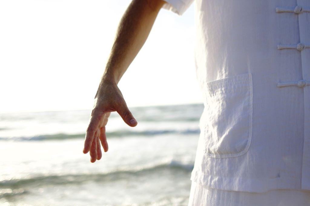 Gesundheitspraxis Oberfranken Qi Gong Übender steht am Strand